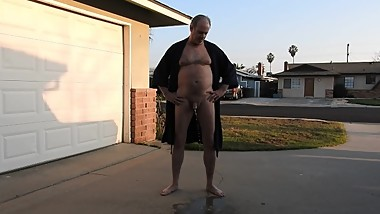 Naked mature man peeing in his driveway in front of the neighbors.