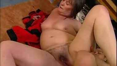 Fat mature Sandora having sex with a guy in a garage.